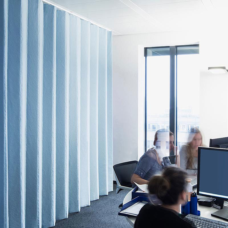 """Der Design Schallabsorber """"Softwall"""" in hellblau in einer Büro-Architektur.."""
